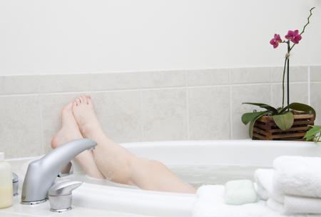 La femme prend un bain chaud contre les douleurs menstruelles