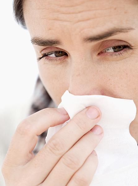 La femme se mouche parce qu'elle est enrhumée.