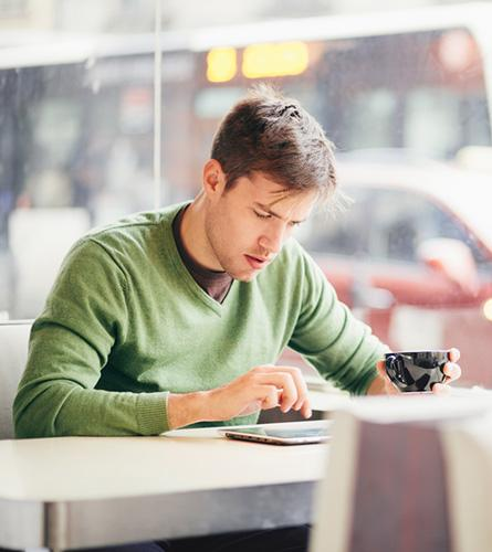 Un jeune homme risque d'avoir les muscles noués parce qu'il passe de longues heures à utiliser la tablette dans une mauvaise position