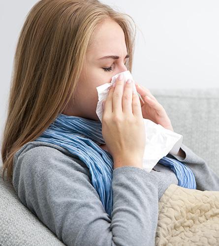 La femme a le nez qui coule car elle souffre d'un rhume