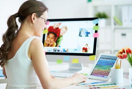 La femme reste longtemps assise au travail, concentrée devant son PC ce qui pourrait lui provoquer des maux de dos si elle adopte une mauvaise posture
