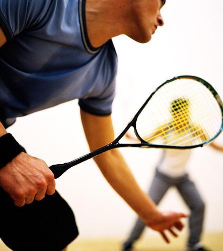 Les hommes jouent au squash. Ce sport est connu pour provoquer des maux de dos